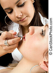 Young beautician applying lipgloss on a woman's lips