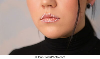 Lip makeup with beads.full hd video - Lips of a young girl...