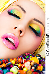 Close-up of beautiful female face with colourful make-up and lips, eyes closed