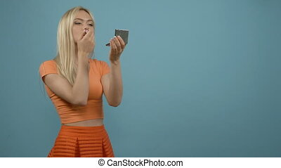 Lips makeup. Smiling blonde woman in orange top applying pomade with mirror, blue background