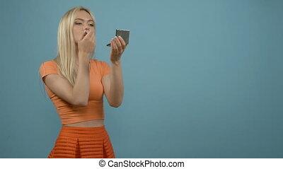 Lips makeup. Smiling blonde woman in orange top applying...