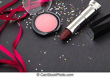 Lipstick and blush on dark stone background