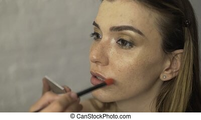 Lipstick being applied to beautiful model s lips with a brush