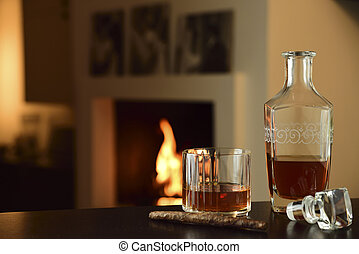 liqueur and cigar in the foreground on table and lit fireplace in the background