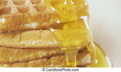Liquid honey floods the edge of the waffles close-up