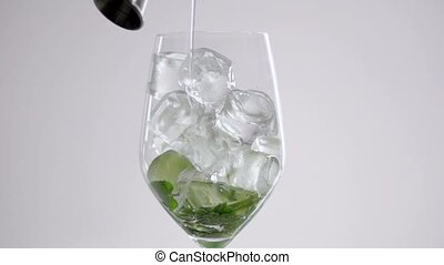 Liquid is poured into a glass with ice cubes and lime and mint leaves.