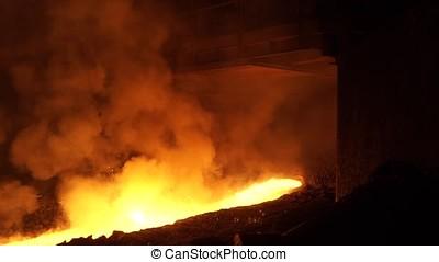 Liquid metal from blast furnace. Liquid metal pouring stream...
