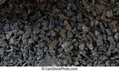 Liquid mortar solution pours on a gravel floor fron a...