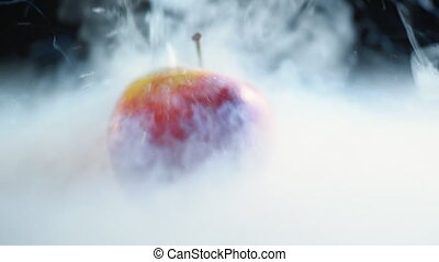 Liquid nitrogen is poured onto a red juicy apple, freezing...