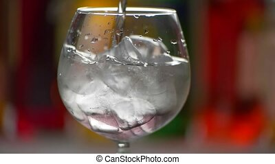 Liquid slowly pouring in glass. Cubes of ice in beverage....