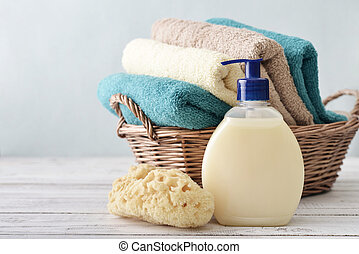 Liquid soap, sponge and towels in a wicker basket on a light...