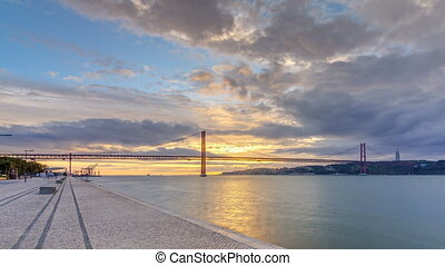 Lisbon city sunrise with April 25 bridge night to day timelapse, River and waterfront early morning