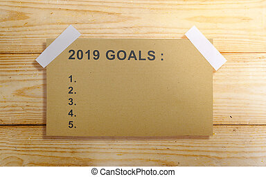 List of 2019 goals in brown paper on wooden wall