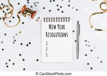 List of new year resolutions in beautiful note pad. Festive...