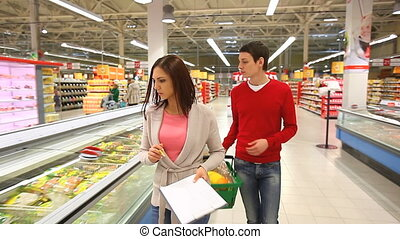 List of products - Young couple doing shopping in...