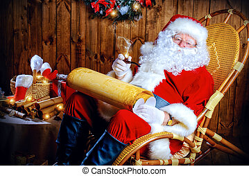 list of wishes - Santa Claus sitting at his wooden house in ...