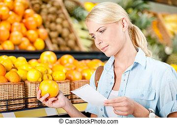 lista de compras, lee, manos, naranja, niña