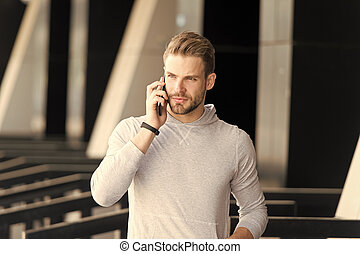 Listen to me. Man beard walks with smartphone, urban background. Man with beard serious face talk smartphone. Guy concentrated answer call on smartphone. Communication concept. Mobile conversation