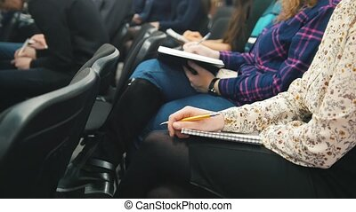 Listeners participating in a lecture - people writing into their notebooks