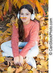 Listening song. Audio file. Educational podcast. Feel joy. Kid girl relaxing near autumn tree with headphones. Music for autumn cozy mood. Autumn playlist concept. Enjoy music outdoors fall warm day