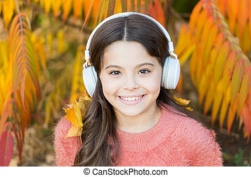 Listening song. Enjoy music outdoors fall warm day. Audio file. Educational podcast. Autumn playlist concept. Feel joy. Kid girl relaxing near autumn tree with headphones. Music for autumn cozy mood