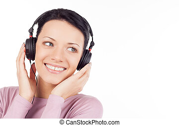 Listening to her favorite music. Beautiful young woman in headphones listening to the music and smiling while isolated on white