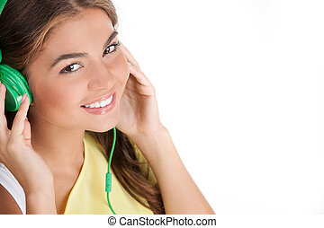Listening to her favourite music. Top view of cheerful young woman in headphones listening to the music while standing isolated on white