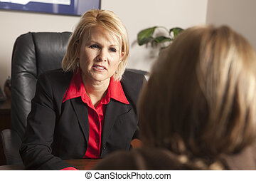 A business woman listening intently to the needs of a client