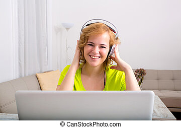 Listening to music on a laptop computer in the evening