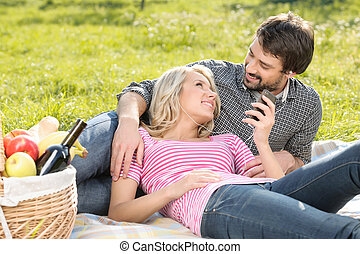 Listening to the music together. Loving young couple listening to the music on picnic together