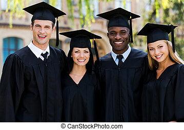 listo, a, brillante, future., cuatro, colegio, graduados, en, trajes de ceremonia de entrega de diplomas, posición, cerca de, uno al otro, y, sonriente