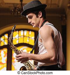 listo, para, improvising., guapo, joven, jazz, hombre estar de pie, con, saxófono, en, el suyo, manos