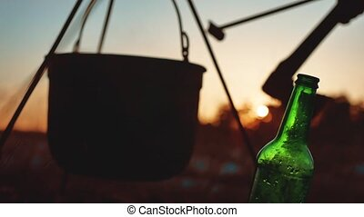 lit a cauldron bonfire a bottle of beer at sunset silhouette...