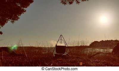 lit campfire hiker halt on a campsite hiker water boils in a...