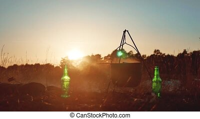 lit campfire on a campsite water boils in a kettle goes smoke sunlight at sunset silhouette rest tourism in the forest nature lifestyle