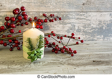 Lit candle and a stick with red berries - A stick of...