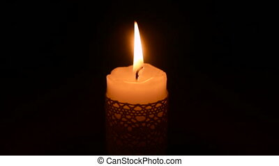 Lit candle in the dark