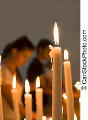 Lit candles detail - Lit candles in a church