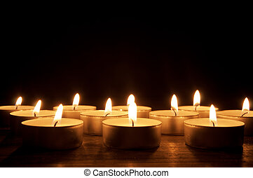 Lit candles  - Rows of lit candles in the dark