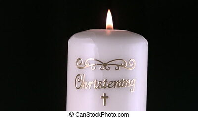 Lit christening candle flickering a