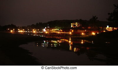 Lit coast with resort at night . Goa