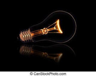 Lit light bulb on black background