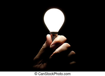 Lit lightbulb held in hand on black