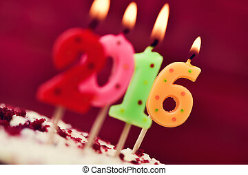 lit number-shaped candles forming number 2016 on a cake