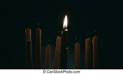 Lit one candle in a dark room, next to not lit candles
