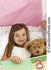 liten flicka, läsning en boka, in blomsterbädd
