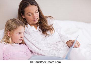 liten flicka, läsning en boka, med, henne, mor
