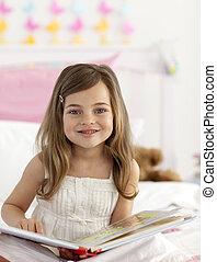 liten flicka, läsning, in blomsterbädd