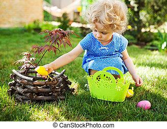 liten flicka, på, en, påsk ägg jaga, på, a, äng, in, fjäder