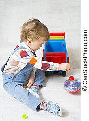 liten pojke, leker, med, a, bil, och, spinning högsta, leksak